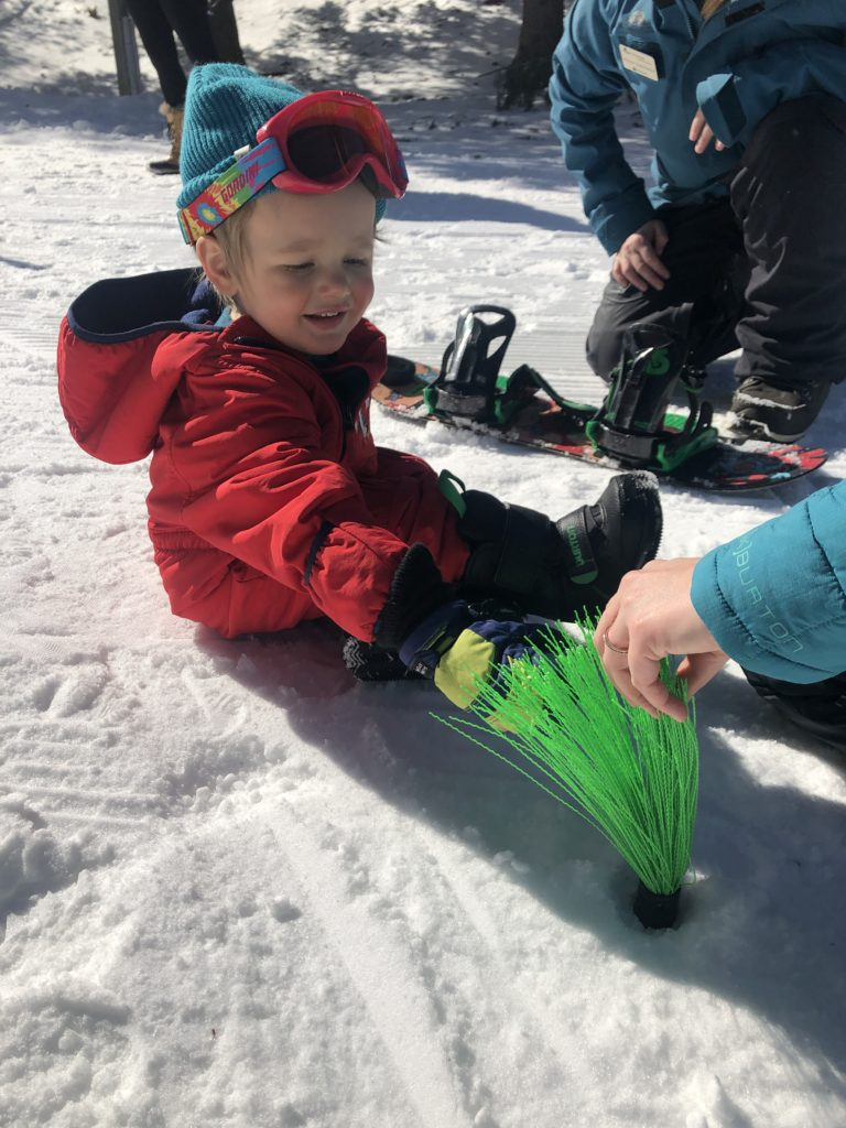 Fun breaks help a toddler handle snowboard lessons