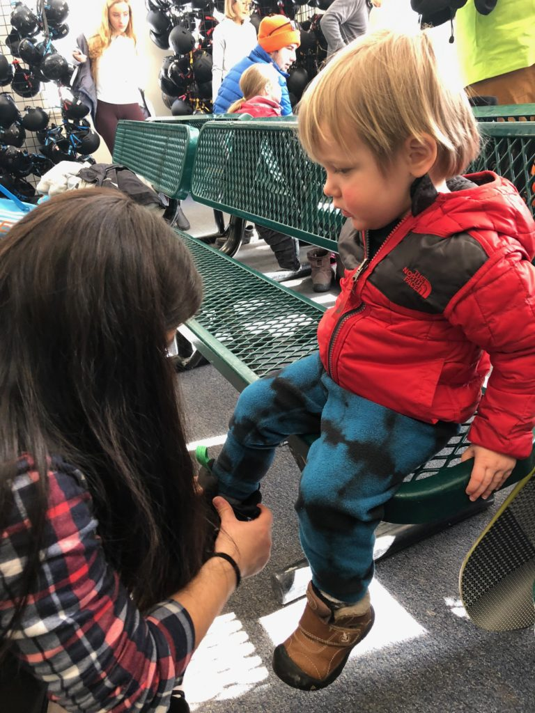 Getting a toddler outfitted for snowboard lessons